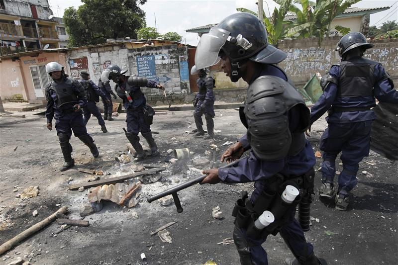 Riot police dismantle a roadblock in Democratic Republic of Congo's capital Kinshasa