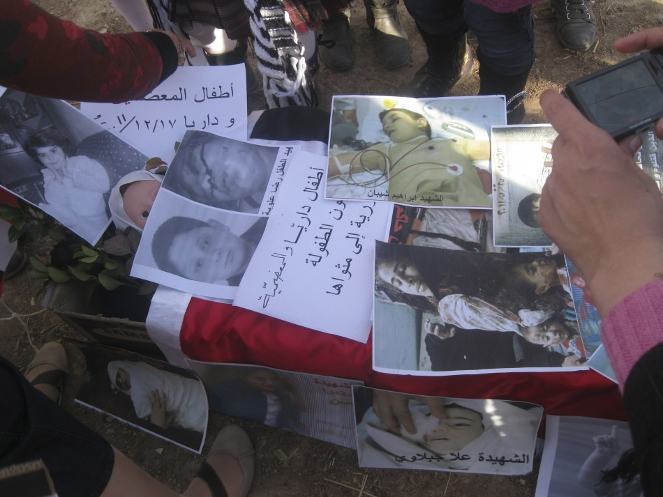 People take pictures of posters during a protest against Syria's President Assad in Daria near Damascus