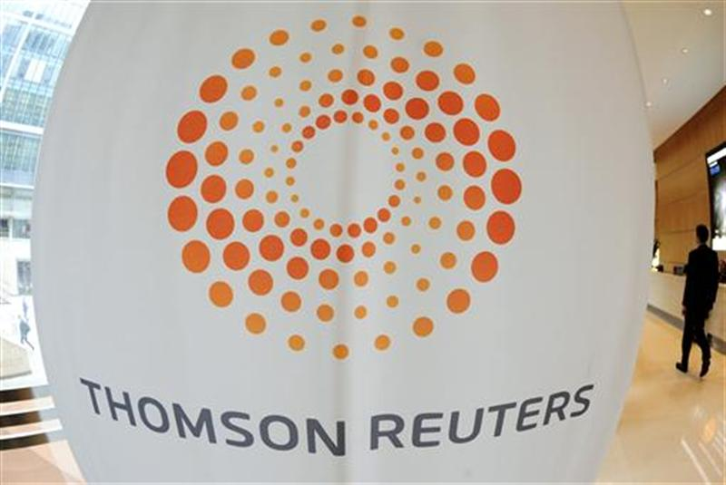 A man walks near a Thomson Reuters logo at the Thomson Reuters building in Canary Wharf in east London