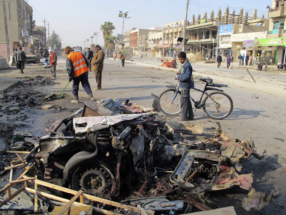 A boy stands near the site of a car bomb attack in Baghdad's Shaab District, northern Baghdad