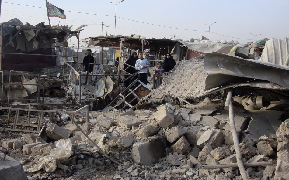 Residents sift throuigh rubble after of a market was bombed in Baghdad's Shula district in northwestern Baghdad
