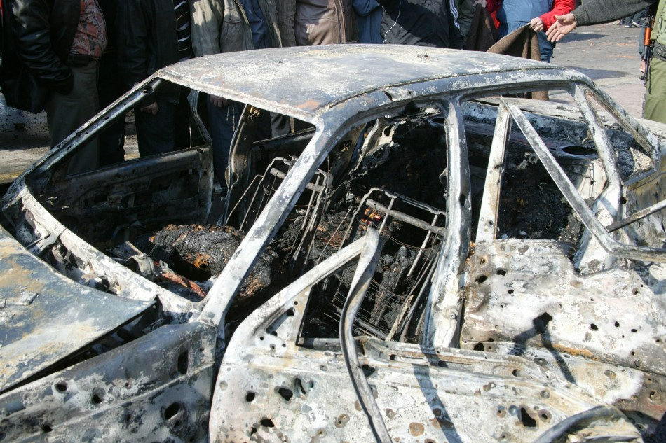 A damaged car is seen where a bomb blew up at security sites in Damascus