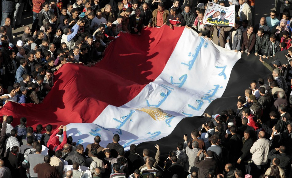 Egyptian protesters shout anti-military council slogans as they hold a national flag in Cairo
