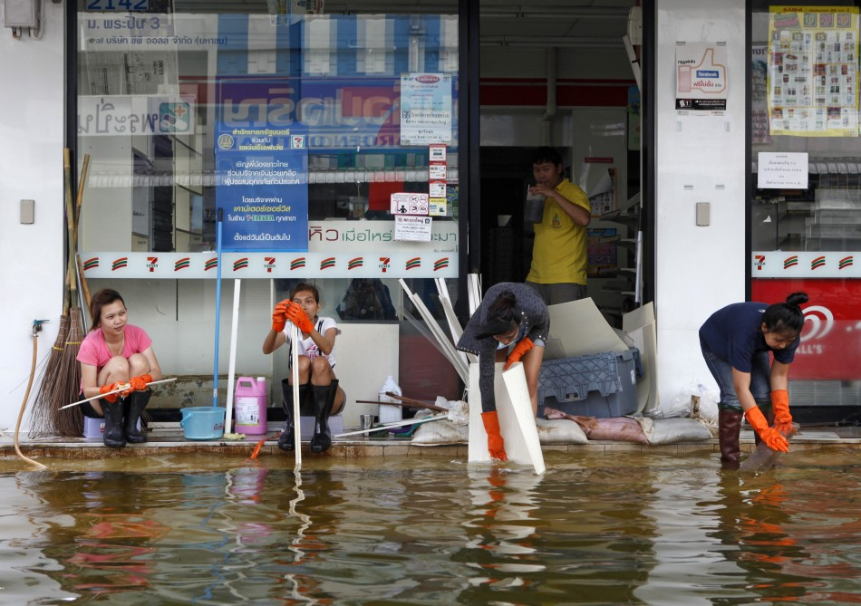 Workers clean a shop as floodwaters recede in Nonthaburi province
