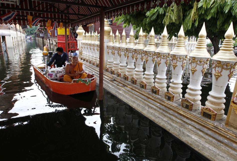 A Buddhist monk takes a boat around a flooded temple in Bangkok