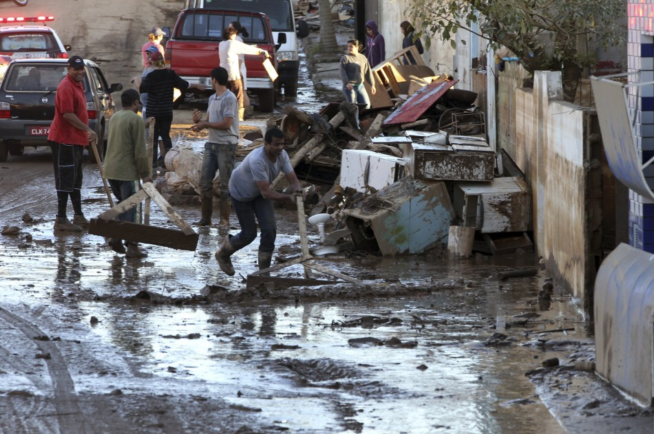 Residents clear a mud-covered street after floodwaters recede in the Ribeira do Iguape riverside suburb of Eldorado
