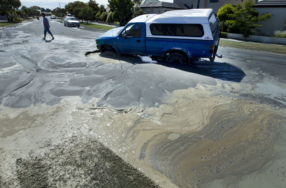 Sewage sweeps past a car trapped in a sink hole after earthquakes in Christchurch