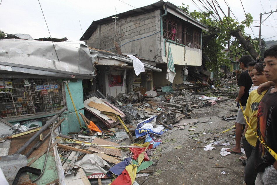 Residents look at the damaged houses after an 18-wheeler truck rammed into a row of houses in Antipolo city