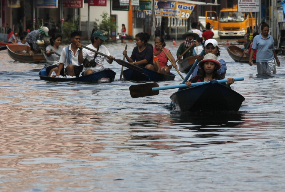 Flood-hit residents paddle through a flooded street in Nonthaburi province