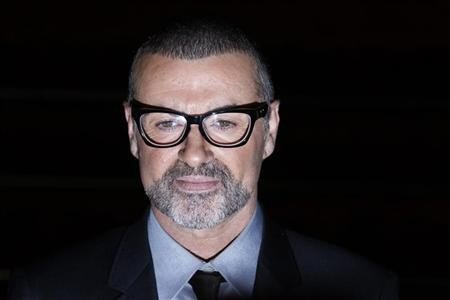 British singer George Michael poses for photographers before a news conference at the Royal Opera House in central