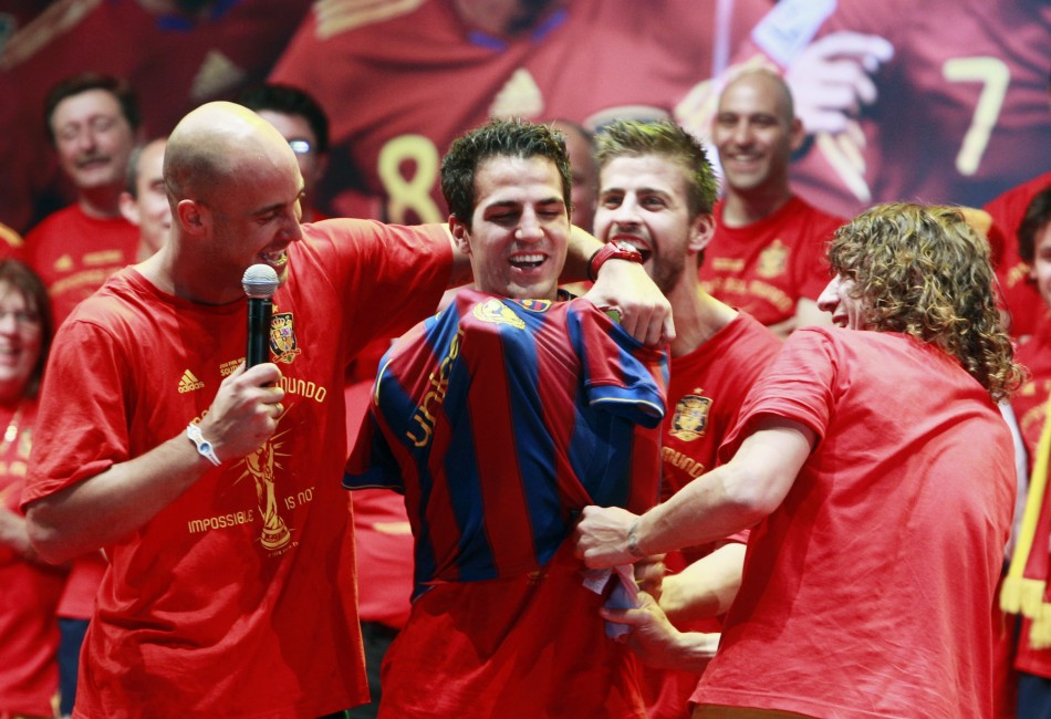 Spain's Pepe Reina and Carles Puyol put a Barcelona shirt on team-mate Cesc Fabregas as they celebrate their victory in Madrid