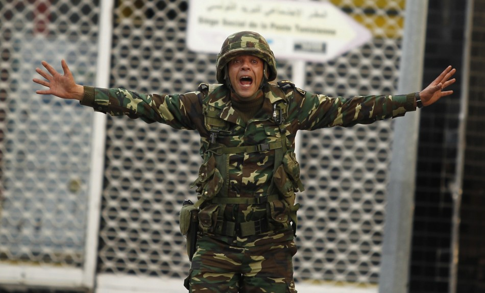 A Tunisian soldier screams to calm protesters