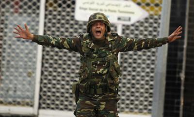 A Tunisian soldier screams to calm protesters