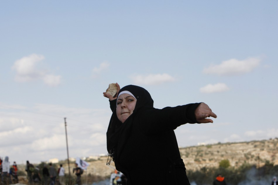 A Palestinian woman pelts a stone at Israeli troops