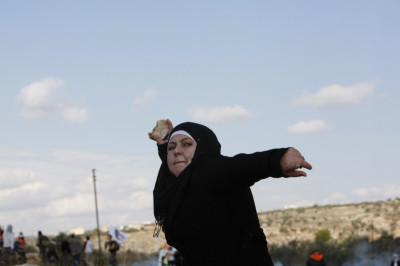 A Palestinian woman pelts a stone at Israeli troops
