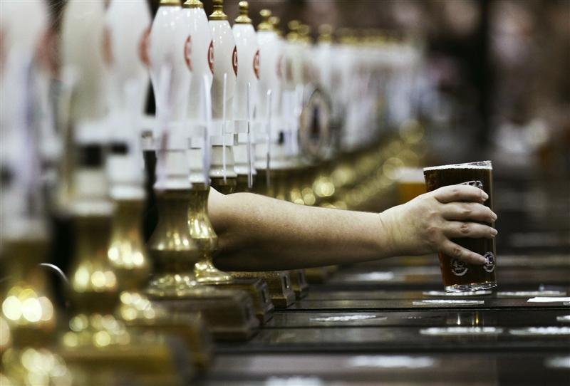 A pint of beer is served through rows of beer pumps at the Campaign For Real Ale Great British Beer Festival at Earls Court in London