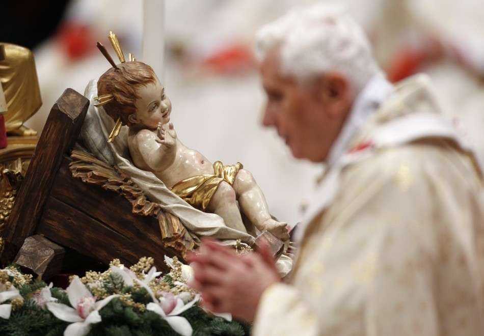 Pope Benedict XVI walks past a figurine of baby Jesus as he leads the Christmas mass in Saint Peter's Basilica