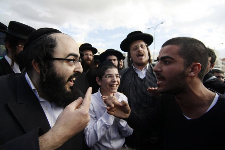 An ultra-Orthodox Jewish man argues with a secular man during a protest