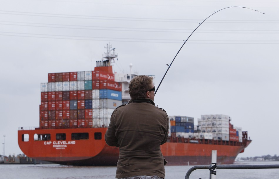 A man fishes while a loaded tanker passes by