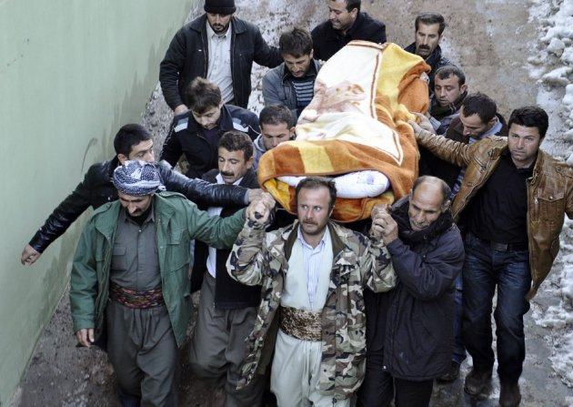 Locals carry a victim, killed in airstrikes, to the morgue of a hospital in Uludere, of the Sirnak province