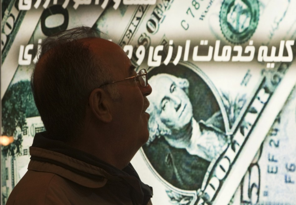 An Iranian man walks past a currency exchange shop in northern Tehran