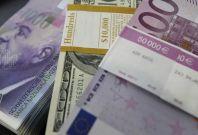 Stacks of Swiss franc, Euro and U.S. dollar banknotes