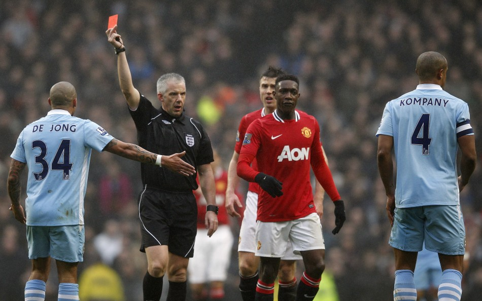 Manchester City's Vincent Kompany (R) is shown a red card by referee Chris Foy