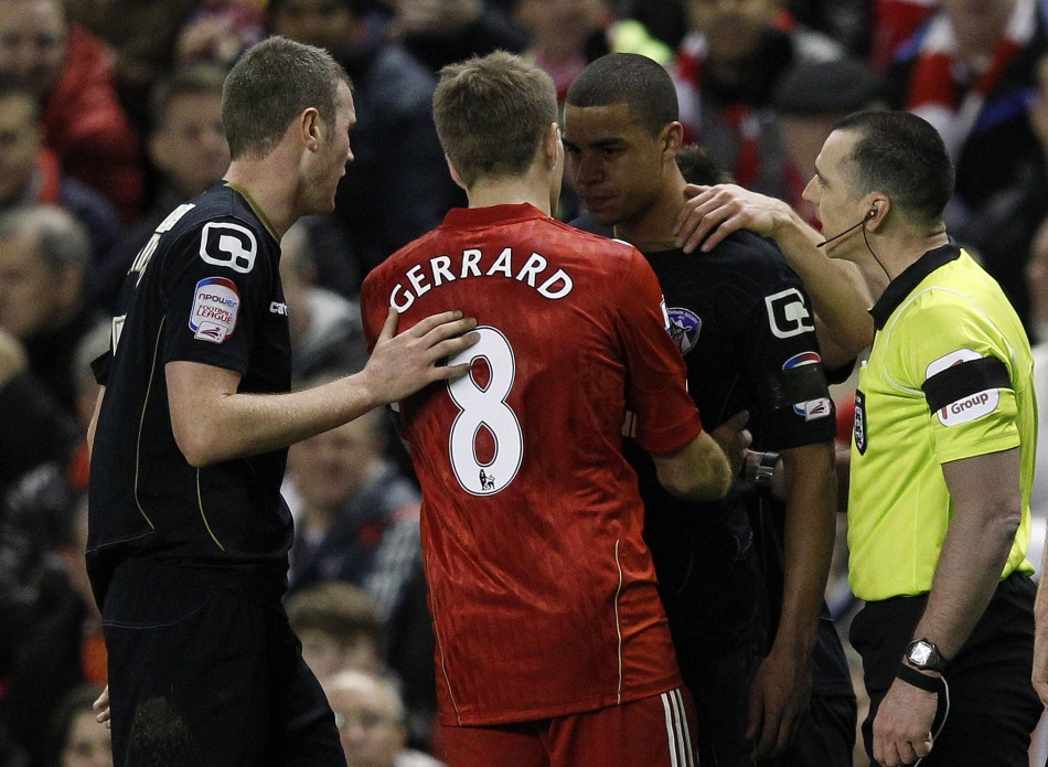 Oldham Athletic's Adeyemi is calmed down by Liverpool's Gerrard and referee Swarbrick after a fan shouted abuse at him during their FA Cup soccer match in Liverpool