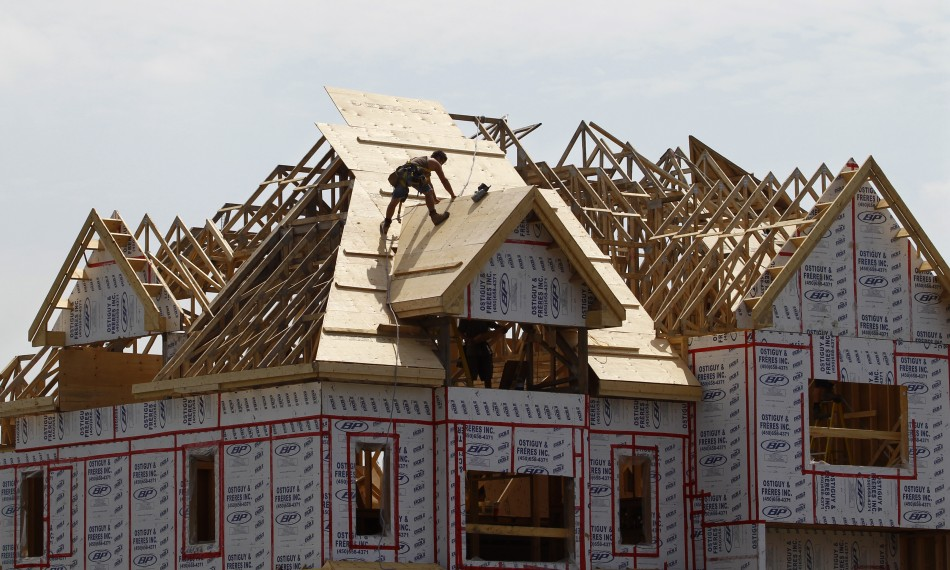 A builder works on the the roof of a new home