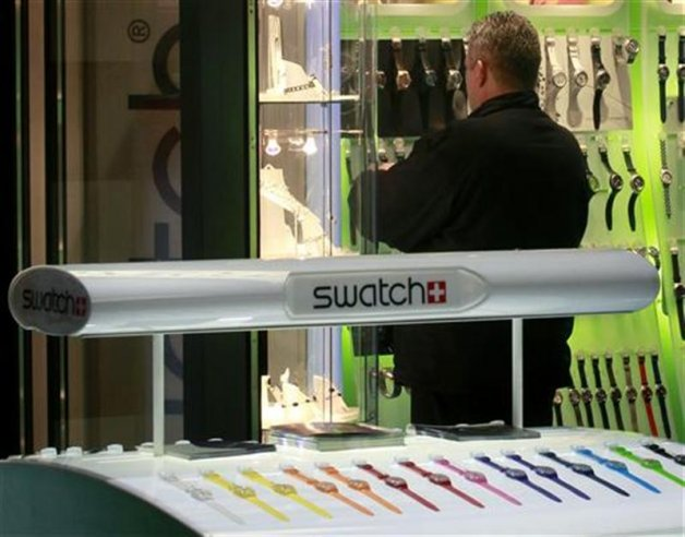 A man stands at a Swatch watch store at Zurich central station