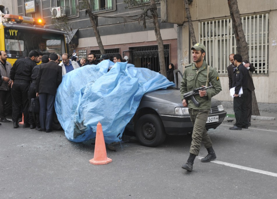 Mostafa Ahmadi-Roshan's car is lifted from the scene after it was blown up by a magnet bomb in Tehran