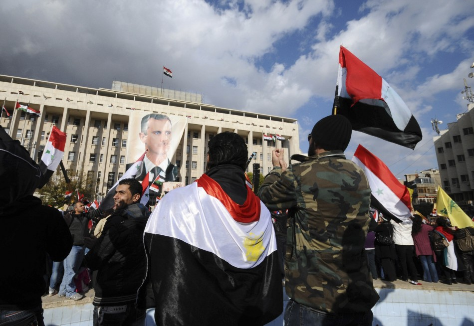 Supporters of Syria's President Bashar al-Assad carry Syrian flags