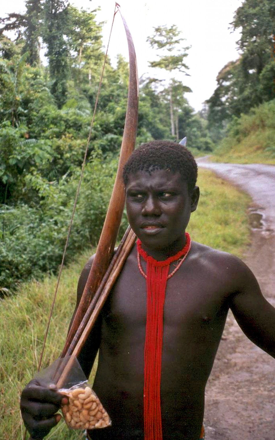 A tribal man with his bow looks on at the Andaman Trunk road in Jarawa reserve