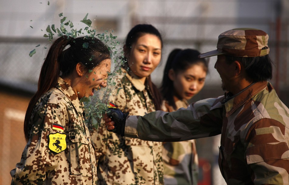 An instructor from Tianjiao Special Guard Consultant Ltd smashes a bottle over a female recruit's head during a training session