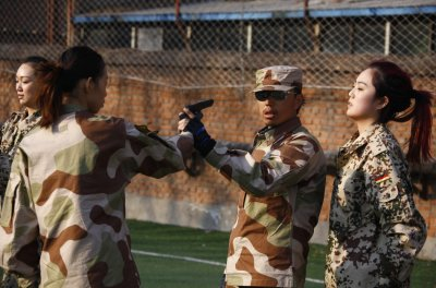 An instructor demonstrates how to disarm an attacker at the boot camp for female bodyguards