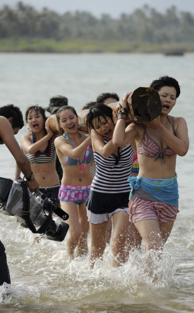 Trainees dressed in swimming suits shoulder a log to build up strength and work as a team
