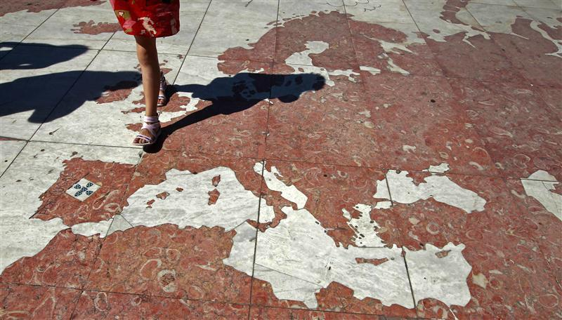 A woman walks on a map of Europe, which is part of a marble world planisphere, in Lisbon August 14, 2011.