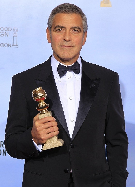 "George Clooney poses with his award for best actor in a motion picure - drama for ""The Descendants,"" backstage in Beverly Hills (Reuters)"