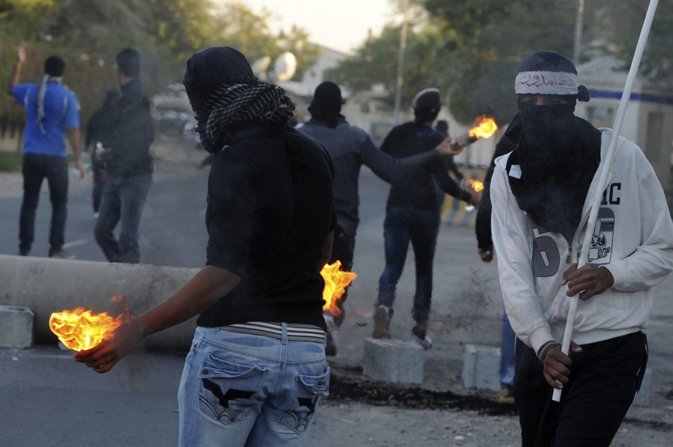 Anti-government protesters hold Molotov cocktails during clashes with police in the village of Barbar