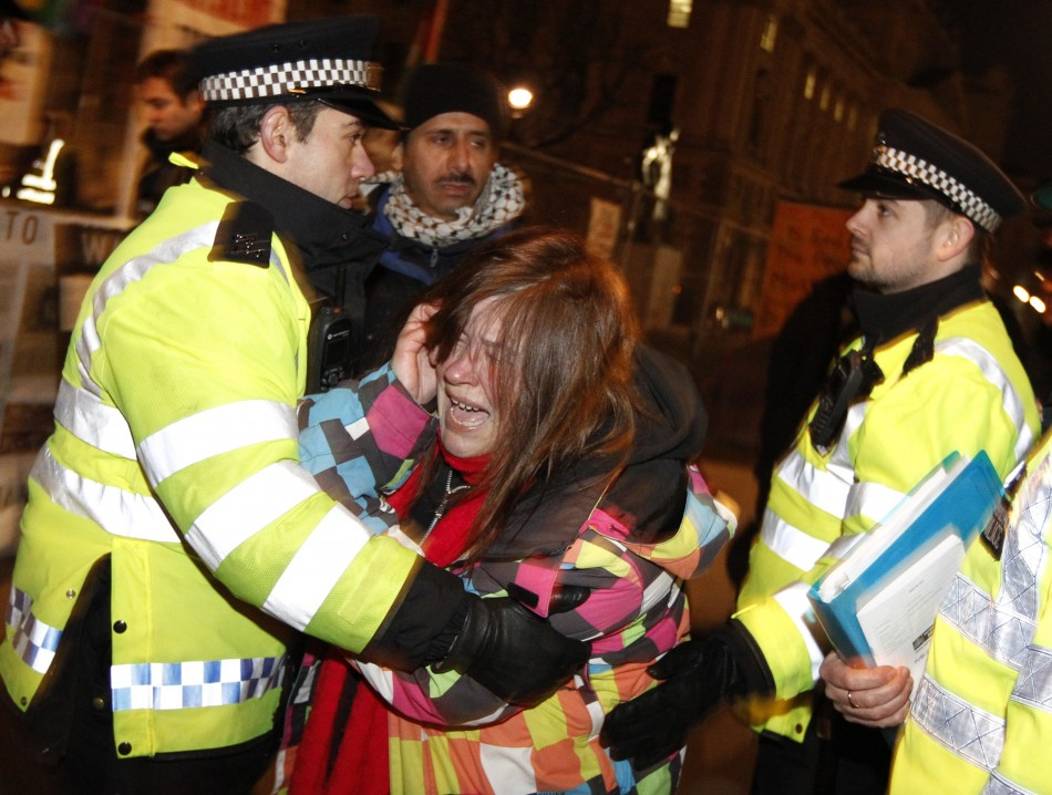 Police move a woman during the Parliament Square eviction