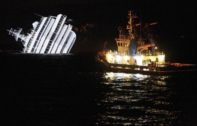An oil removal ship is seen next to the Costa Concordia cruise ship