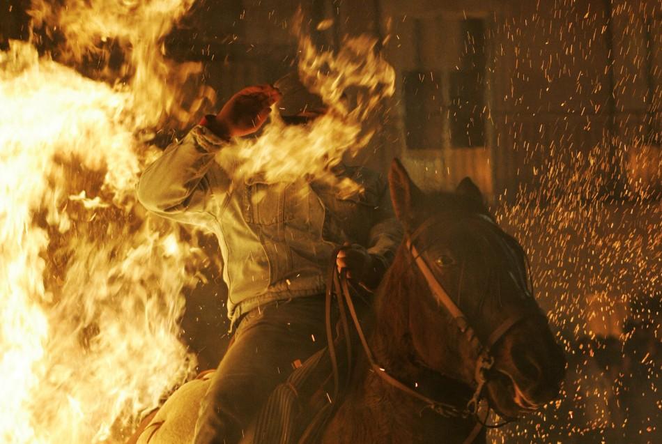 Flames cover a mans face as he races through the fire at the Luminarias festival in San Bartoleme de los Pinares