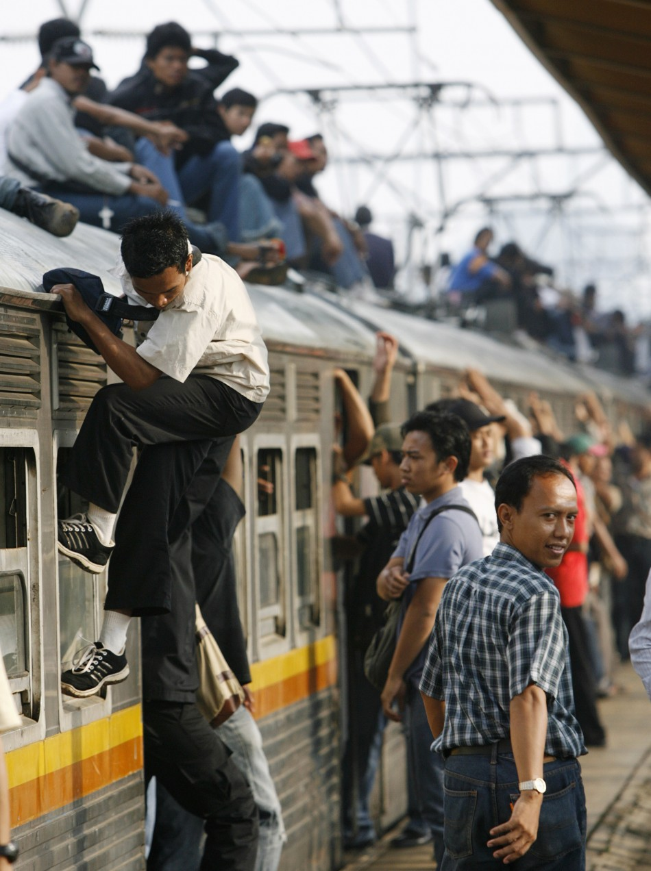 Indonesians climb on to the top of a train, a practice known as roof riding or train surfing
