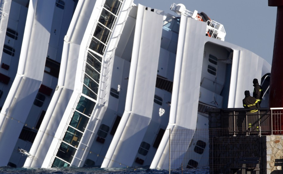 Two firefighters watch the Costa Concordia cruise ship that ran aground off the west coast of Italy, at Giglio island
