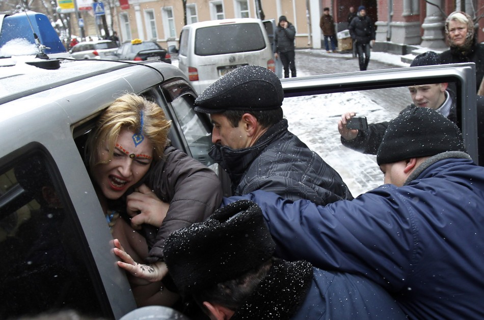 An activist from women's rights group Femen is detained during a protest outside the residence of the Indian ambassador in Kiev