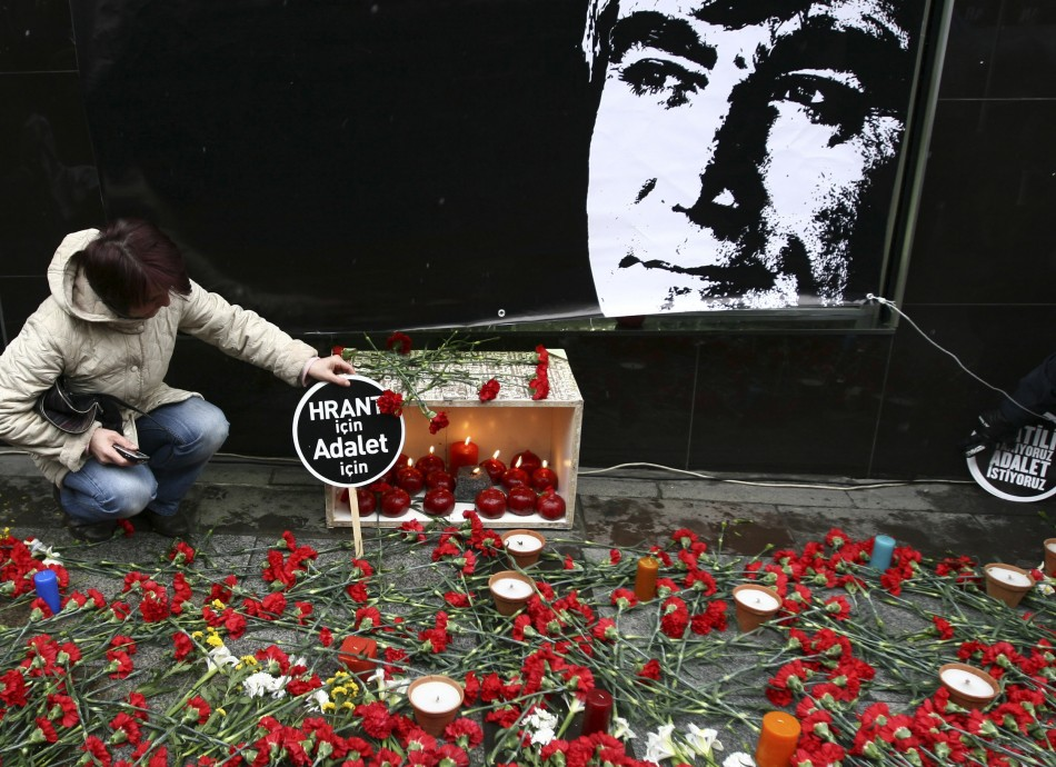 A protester leaves a banner next to the portrait of Hrant Dink in front of the office of the Agos newspaper