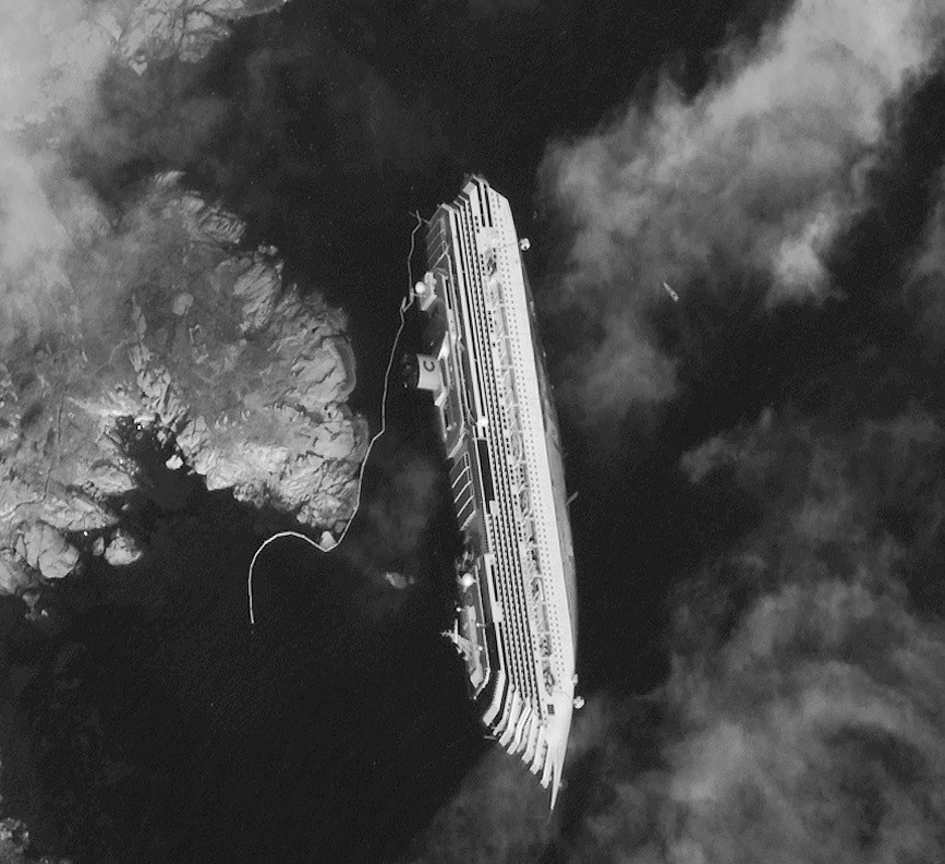 A satellite image of the Costa Concordia half-submerged in water