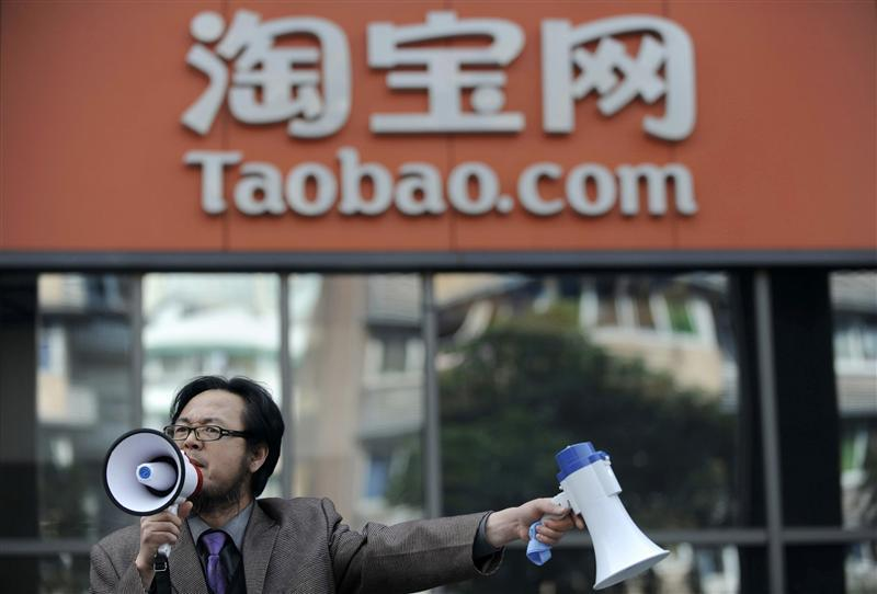 A man holds loudspeakers at the entrance to the Taobao office during a protest in Hangzhou