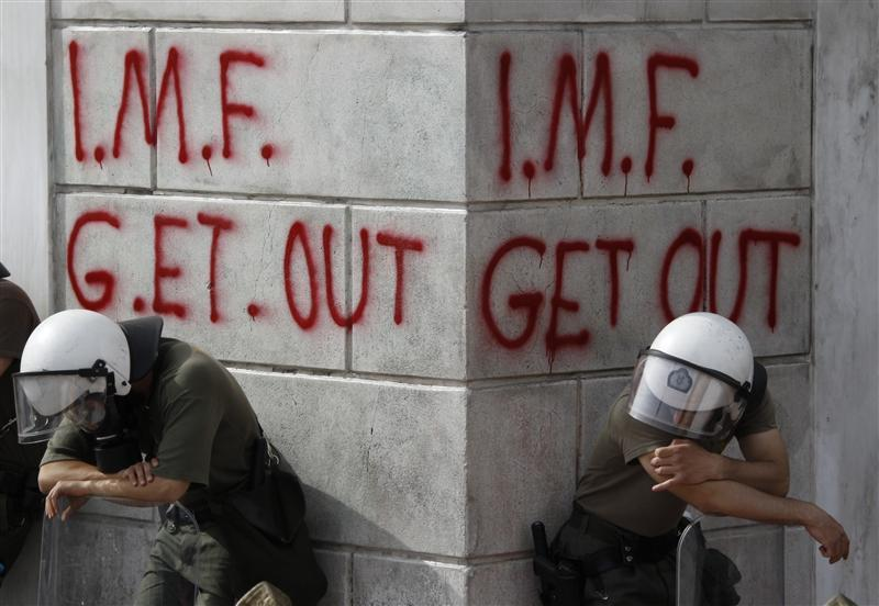 Greek riot policemen rest in front of graffiti during violent demonstrations over austerity measures in Athens