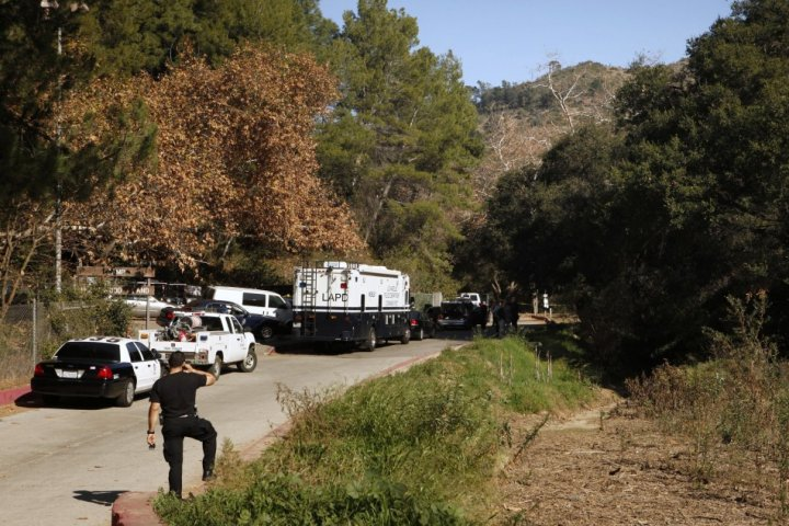 Los Angeles County coroners and Los Angeles police officers are seen at the crime scene in Bronson Canyon (Reuters)